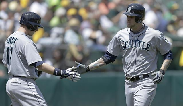 Seattle Mariners' Corey Hart, right, is congratulated by Justin Smoak, left, after Hart hit a home run off Oakland Athletics' Dan Straily in the second inning of a baseball game Wednesday, May 7, 2014, in Oakland, Calif. (AP Photo/Ben Margot)