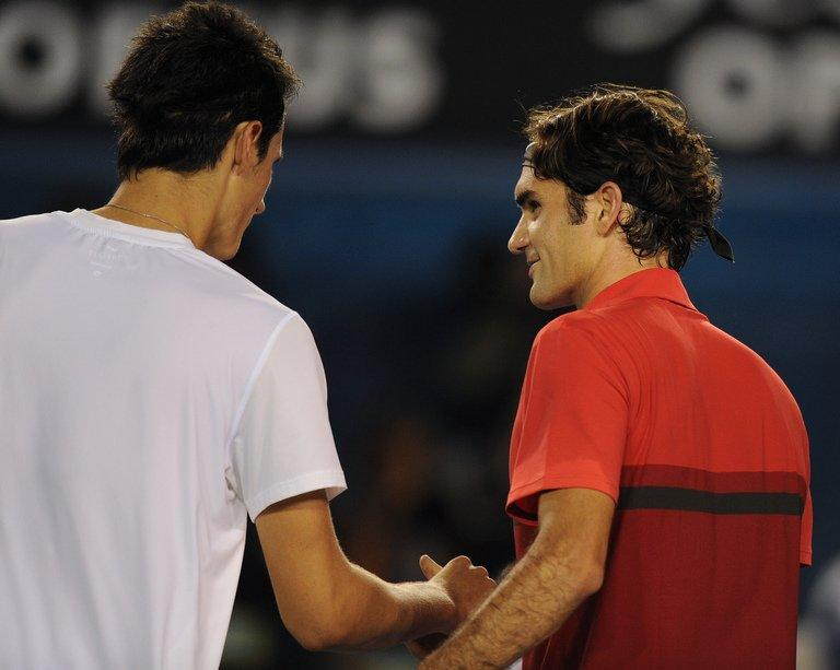 Roger Federer (R) shakes hands with Bernard Tomic after their fourth-round match on January 22, 2012