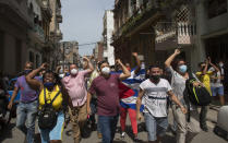 CORRECTS TO PRO-GOVERNMENT SUPPORTERS - Government supporters shout slogans as anti-government protesters march in Havana, Cuba, Sunday, July 11, 2021. Hundreds of demonstrators went out to the streets in several cities in Cuba to protest against ongoing food shortages and high prices of foodstuffs. (AP Photo/Ismael Francisco)