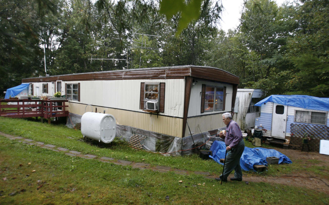 In this Sept. 15, 2011 photo, Bill Ricker, 74, walks to his trailer in Hartford, Maine. Ricker, who has two college degrees, has worked as an electronics repairman, a pastor and a TV cameraman. He and his first wife had seven children. Now he receives food stamps and heating fuel assistance and gets donations from a local food pantry. (AP Photo/Robert F. Bukaty)
