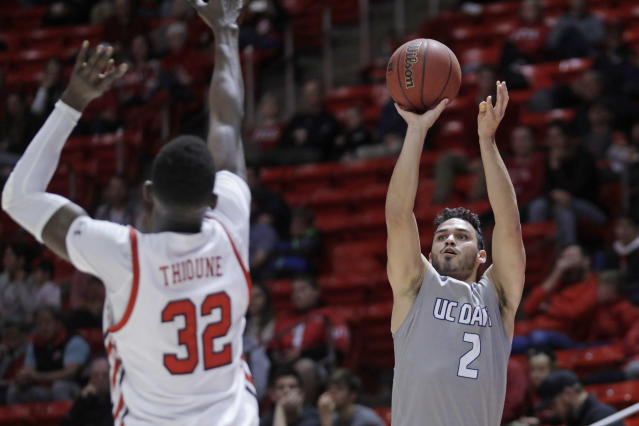 UC Davis guard Stefan Gonzalez (2) shoots as Utah center Lahat Thioune (32) defends during the first half of an NCAA college basketball game Friday, Nov. 29, 2019, in Salt Lake City. (AP Photo/Rick Bowmer)