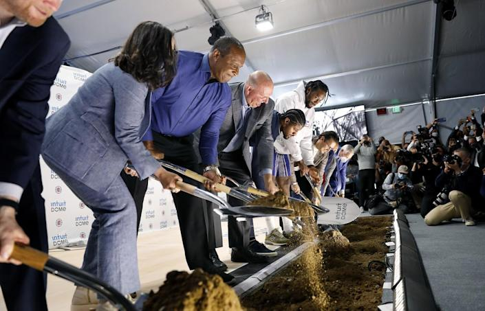 Clippers officials and dignitaries break ground with ceremonial shovels at the site of the team's new arena.