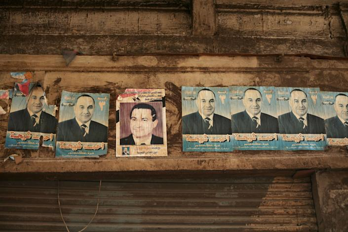 A defaced poster of former Egyptian president Hosni Mubarak, third left, is seen in Old Cairo, Egypt, Thursday, May 24, 2012. In a wide-open race that will define the nation's future political course, Egyptians voted Thursday on the second day of a landmark presidential election that will produce a successor to longtime authoritarian ruler Mubarak. (AP Photo/Manu Brabo)