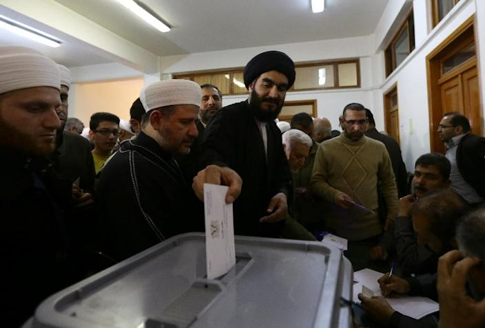 Around 7,200 polling stations opened at 0400 GMT in government-held areas, where about 60 percent of the Syrian population lives (AFP Photo/Louia Beshara)