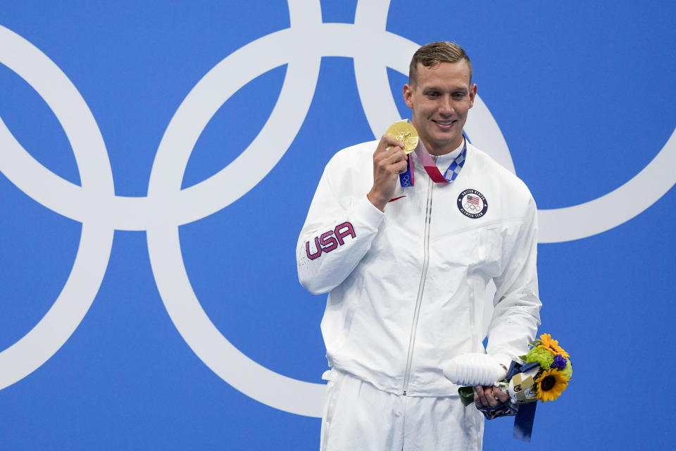 Caeleb Dressel, of the United States, poses with the gold medal after winning the men's 100-meter freestyle final at the 2020 Summer Olympics, Thursday, July 29, 2021, in Tokyo, Japan. (AP Photo/Charlie Riedel)