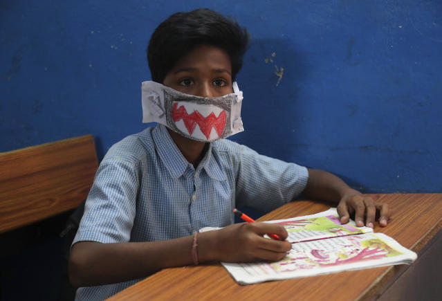A student attends a class wearing a handmade paper mask to protect himself from the wide spread of coronavirus in a government school in Hyderabad.
