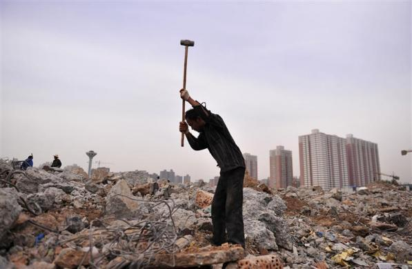 A laborer swings a sledgehammer to smash concrete to recycle steel bars at a demolition site near a residential complex in Xi'an, Shanxi province June 8, 2012.
