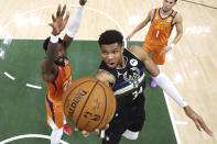Milwaukee Bucks' Giannis Antetokounmpo shoots next to Phoenix Suns' Deandre Ayton, left, during the second half of Game 6 of basketball's NBA Finals, Tuesday, July 20, 2021, in Milwaukee. (Justin Casterline/Pool Photo via AP)