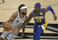 San Antonio Spurs' Patty Mills (8) drives against Indiana Pacers' Caris LeVert during the first half of an NBA basketball game Saturday, April 3, 2021, in San Antonio. (AP Photo/Darren Abate)