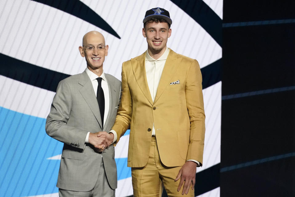 Franz Wagner, right, poses for a photo with NBA Commissioner Adam Silver after being selected eighth overall during the NBA basketball draft, Thursday, July 29, 2021, in New York. - Credit: AP