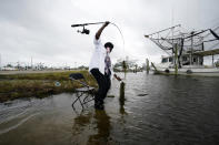 Minnie Lewis fishes for crabs before the wind and waves kick up, in Chalmette, La., Wednesday, Oct. 28, 2020. Hurricane Zeta is expected to make landfall this afternoon as a category 2 storm. (AP Photo/Gerald Herbert)