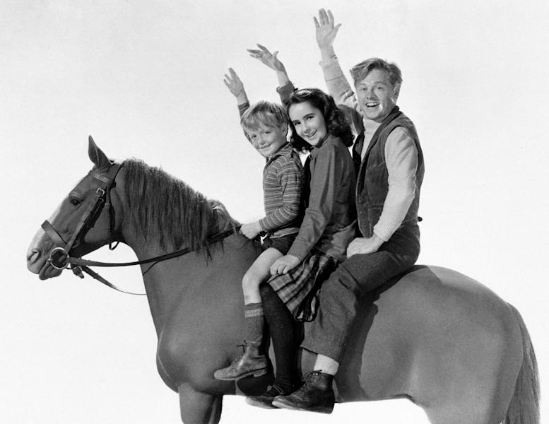"This 1945 file publicity image for the film ""National Velvet,"" shows, from left, actors Butch Jenkins, Elizabeth Taylor and Mickey Rooney. Rooney, a Hollywood legend whose career spanned more than 80 years, died Sunday, April 6, 2014, at his North Hollywood, Calif. home. He was 93. (AP Photo/File)"
