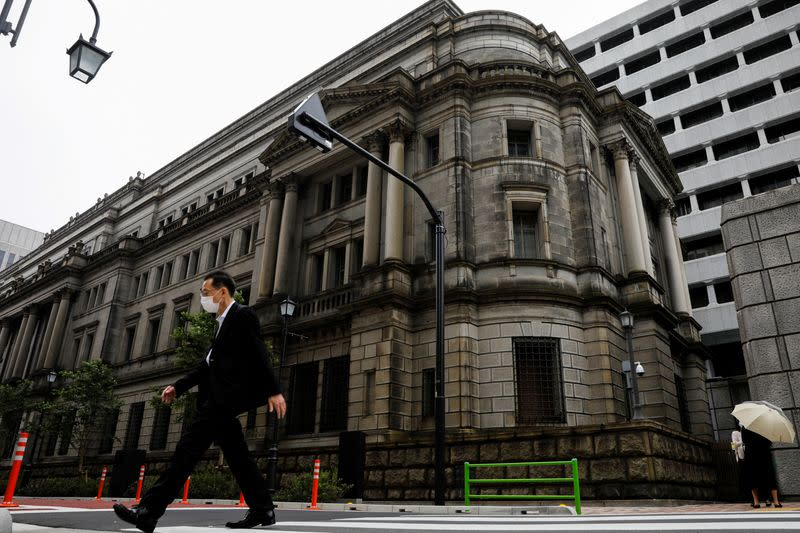 FILE PHOTO: A man wearing a protective mask walks past the headquarters of Bank of Japan amid the coronavirus disease (COVID-19) outbreak in Tokyo