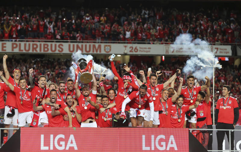 Benfica head coach Bruno Lage, right, watches as team captain Jardel lifts the trophy after the Portuguese league last round soccer match between Benfica and Santa Clara at the Luz stadium in Lisbon, Saturday, May 18, 2019. Benfica won 4-1 to clinch the championship title. (AP Photo/Armando Franca)