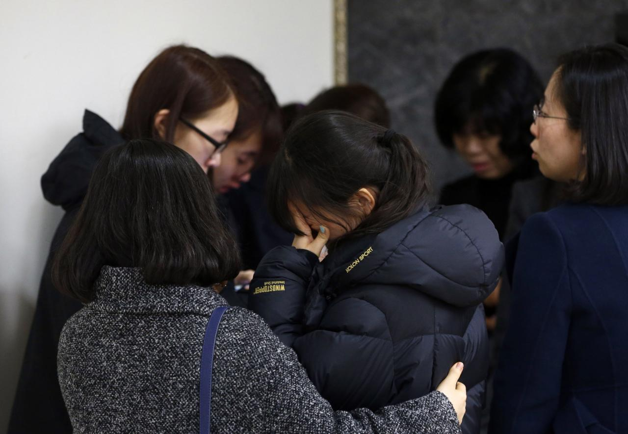 Friends of victims who were killed when a resort building collapsed, react after they paid their tribute outside a group memorial altar in Gyeongju, about 375 km (235 miles) southeast of Seoul February 18, 2014. Ten people attending a welcoming party for new university students were killed when a building at a South Korean mountain resort collapsed late on Monday, emergency officials said, trapping dozens in snow and rubble for several hours. About 560 students had gathered in the auditorium of the golf resort in the mountains in the city of Gyeongju, around 375 km (235 miles) southeast of Seoul. Heavy snow had built up on the roof of the prefabricated building, causing it to collapse, fire department officials said. REUTERS/Kim Hong-Ji (SOUTH KOREA - Tags: DISASTER SOCIETY)