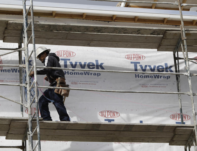 In this Feb. 16, 2011 photo, a construction worker uses Dupont Tyvek Home Wrap at a housing complex in Palo Alto, Calif. The Dupont Co. is raising its 2011 earnings guidance after strong volume growth across all business segments led to an increase in first-quarter earnings Thursday, April 21, 2011.(AP Photo/Paul Sakuma)