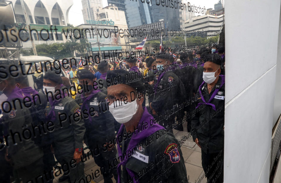 Police officers and supporters of the Thai monarchy are reflected on the sign of the German Embassy in central Bangkok, Thailand Monday, Oct. 26, 2020. The royalists gathered to defend pro-democracy protesters' contention that King Maha Vajiralongkorn spends much of his time in Germany conducting Thai political activities. German government officials have recently expressed concern over political activities the king might be conducting on the Germany's soil. (AP Photo/Gemunu Amarasinghe)