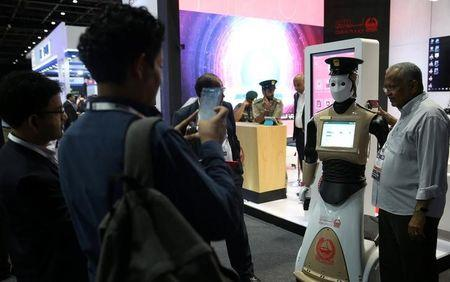 A visitor has a picture taken wtih an operational robot policeman at the opening of the 4th Gulf Information Security Expo and Conference (GISEC) in Dubai, United Arab Emirates, May 22, 2017. Picture taken May 22, 2017. REUTERS/Stringer