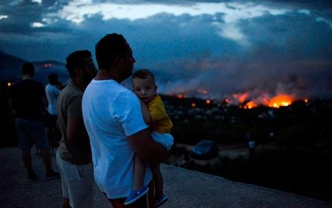 A man holds his son as a wildfire burns in the town of Rafina, near Athens - Credit: AFP