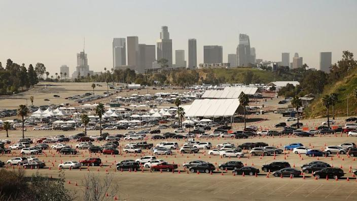 Los Angeles, California-February 25: Vehicles circumvent their way through the parking lot at Los Angeles Dodgers Stadium. Vaccination for COVID-19 is one of the largest vaccinations in the country. It is one of five municipal vaccination sites in collaboration with actor Sean Penn's non-profit organization