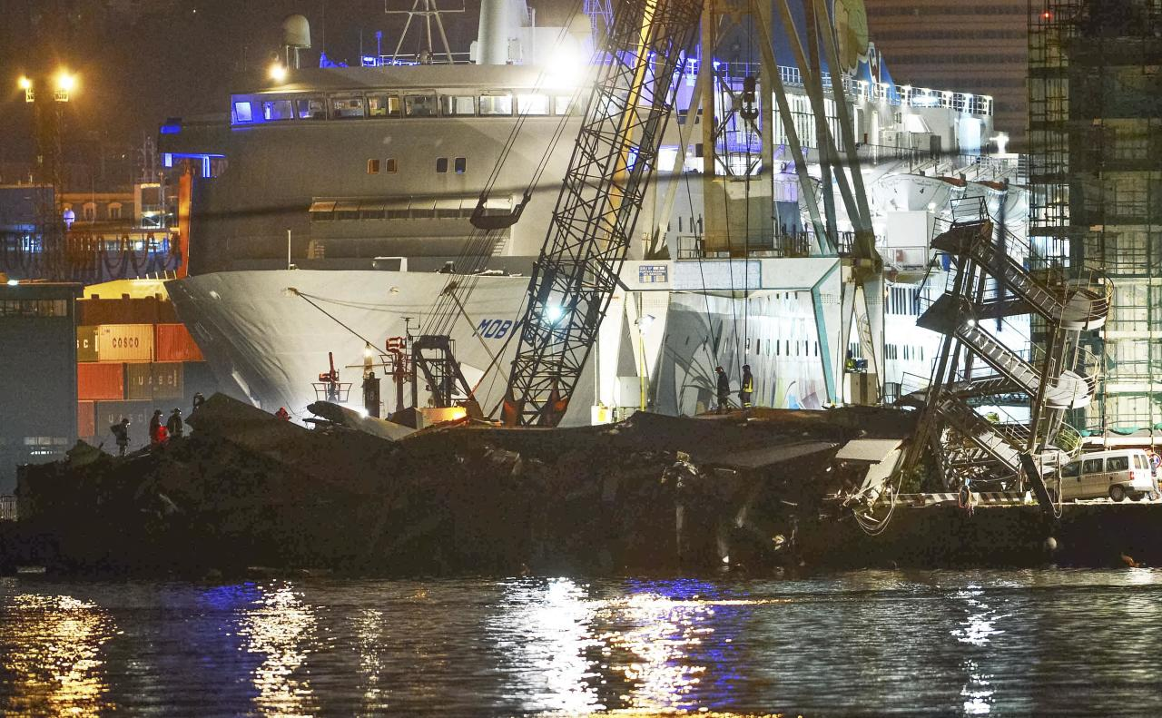 Rescuers search what is left of the control tower of the port of Genoa, northern Italy, after it collapsed when a cargo ship slammed into it killing at least three people, Tuesday, May 7, 2013. A half-dozen people remain unaccounted for early Wednesday, after a cargo ship identified as the Jolly Nero of the Ignazio Messina & C. SpA Italian shipping line, slammed into the port. (AP Photo/Francesco Pecoraro)