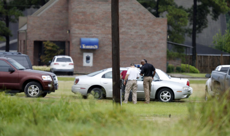 Louisiana law officers inspect a vehicle outside a Tensas State Bank branch during a hostage situation in St. Joseph, La., Tuesday, Aug. 13, 2013. A man whose family owns a store across the street from the bank took three bank employees hostage, and a state police negotiator has been talking to him for hours, police said. (AP Photo/Rogelio V. Solis)