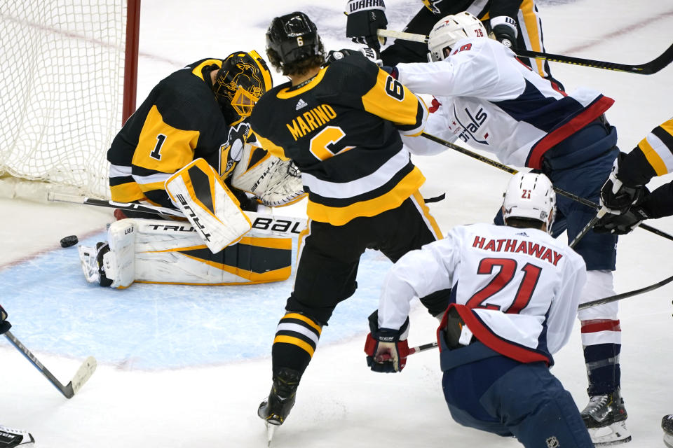 Washington Capitals' Nic Dowd (26) puts the puck behind Pittsburgh Penguins goaltender Casey DeSmith (1) for a goal during with Penguins' John Marino (6) defending during the first period of an NHL hockey game in Pittsburgh, Sunday, Jan. 17, 2021. (AP Photo/Gene J. Puskar)