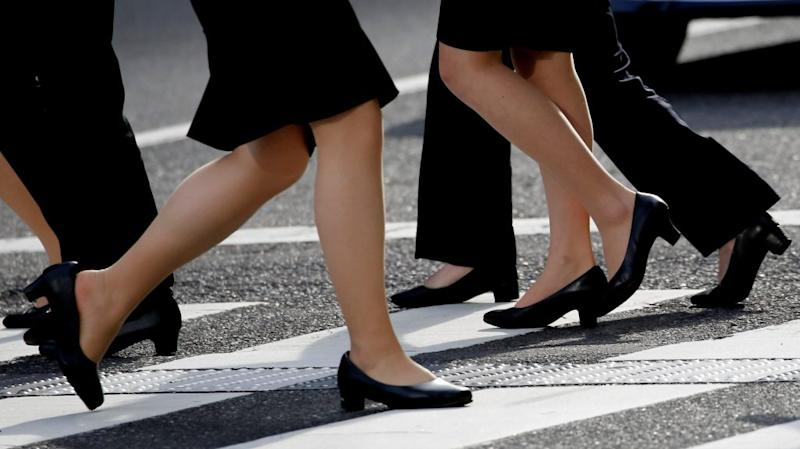 Women in high heels walk at a business district in Tokyo