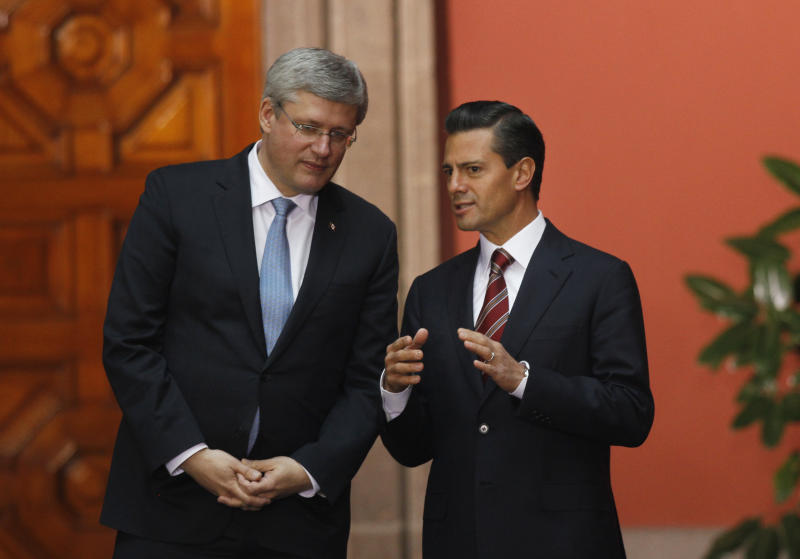 Mexico's President Enrique Pena Nieto, right, with Canada's Prime Minister Stephen Harper pose for photographers after giving a joint news conference at the National Palace in Mexico City, Tuesday, Feb. 18, 2014. The two met in a warm-up of sorts for Wednesday, when the they will join U.S. President Barack Obama at their North American leaders' one-day summit. (AP Photo/Marco Ugarte)