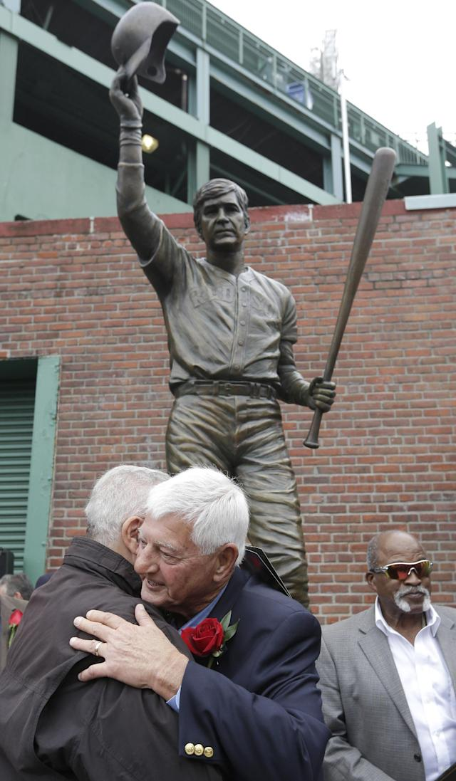 Hall of Famer Carl Yastrzemski, center, hugs former Boston Red Sox's Ted Lepcio, left, during a ceremony held to unveil a statue of Yastrzemski Sunday, Sept. 22, 2013, at Fenway Park in Boston. Former Red Sox's Luis Tiant stands behind right. (AP Photo/Steven Senne)
