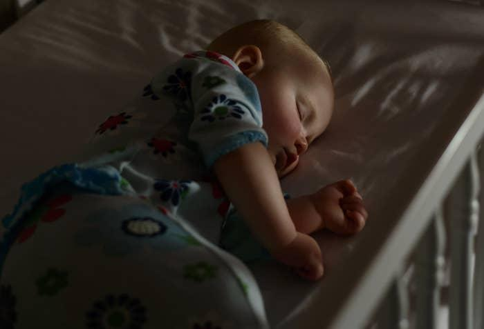 A baby sleeps in a crib in darkness