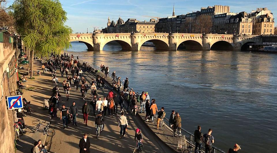 People walk on the banks of the river Seine in Paris on March 15, 2020.