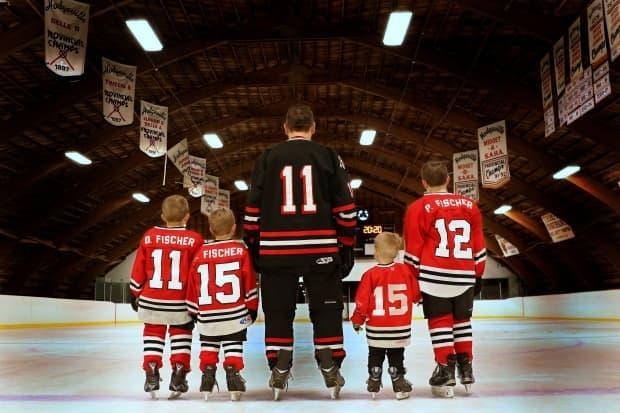 David Fischer, a 39-year-old farmer from southern Saskatchewan, stands on the blue line at Hodgeville rink with his four sons, Declan, Emmett, Nate and Porter to pose for a photo by his wife, Candice. Fischer helps organize a community fundraiser every year to generate tens of thousands of dollars to cover costs and repairs at the rink, hall, and golf course, as well as a new fire truck. (Shot by Candice - image credit)