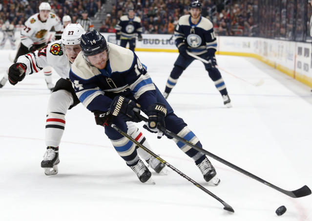 Columbus Blue Jackets forward Gustav Nyquist, right, of Sweden, controls the puck in front of Chicago Blackhawks defenseman Adam Boqvist, of Sweden, during the second period of an NHL hockey game in Columbus, Ohio, Sunday, Dec. 29, 2019. (AP Photo/Paul Vernon)