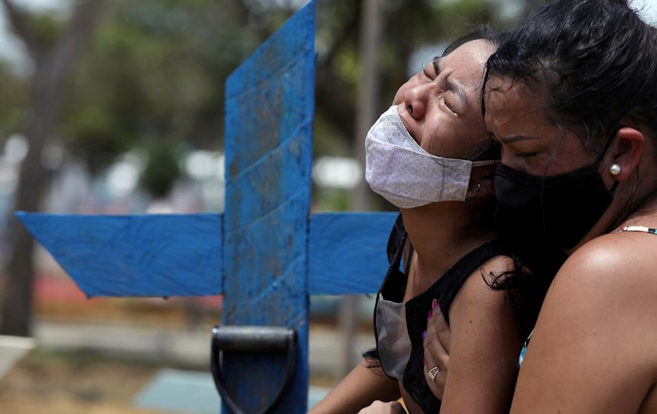 Kelvia Andrea Goncalves, 16, is supported by her aunt Vanderleia dos Reis Brasao, 37, as she reacts during the burial of her mother Andrea dos Reis Brasao, 39, who passed away due to the coronavirus disease (COVID-19) at Delphina Aziz hospital, at the Parque Taruma cemetery in Manaus, Brazil, January 17, 2021. REUTERS/Bruno Kelly     TPX IMAGES OF THE DAY