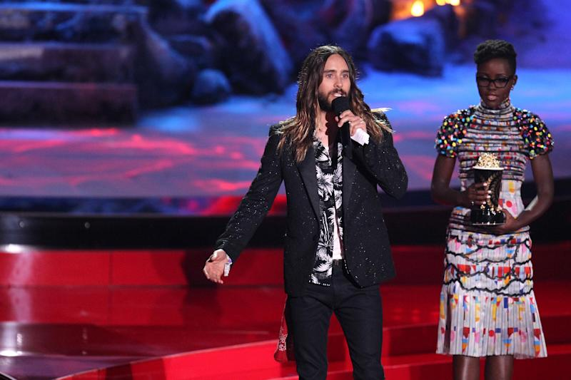 """Lupita Nyong'o, right, looks on as Jared Leto accepts the award for best on screen transformation for """"Dallas Buyers Club"""" at the MTV Movie Awards on Sunday, April 13, 2014, at Nokia Theatre in Los Angeles. (Photo by Matt Sayles/Invision/AP)"""