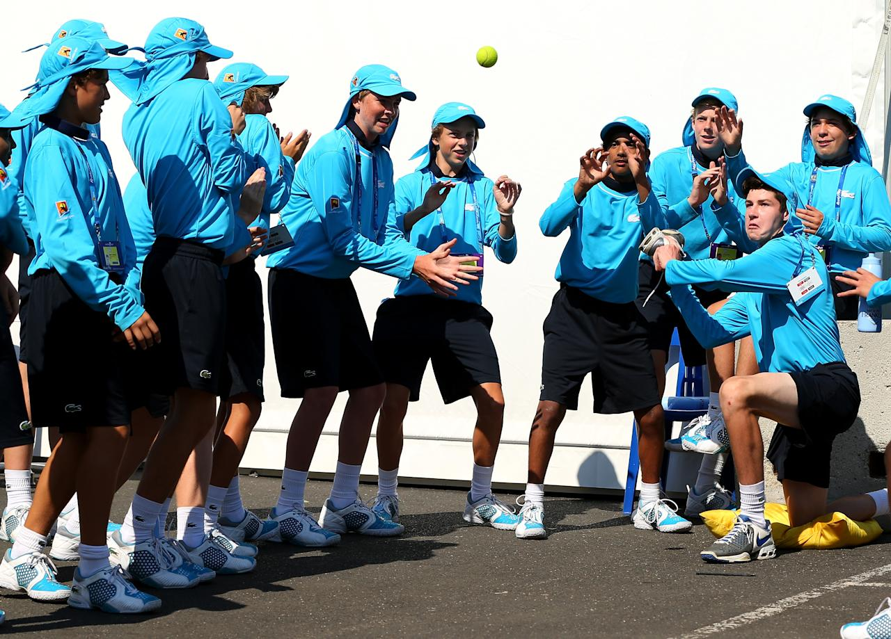 MELBOURNE, AUSTRALIA - JANUARY 20:  Ballboys play cricket with a sneaker and tennis ball during a break on day seven of the 2013 Australian Open at Melbourne Park on January 20, 2013 in Melbourne, Australia.  (Photo by Michael Dodge/Getty Images)