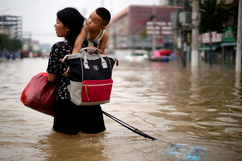 FILE PHOTO: Woman carrying a child and belongings wades through floodwaters following heavy rainfall in Zhengzhou