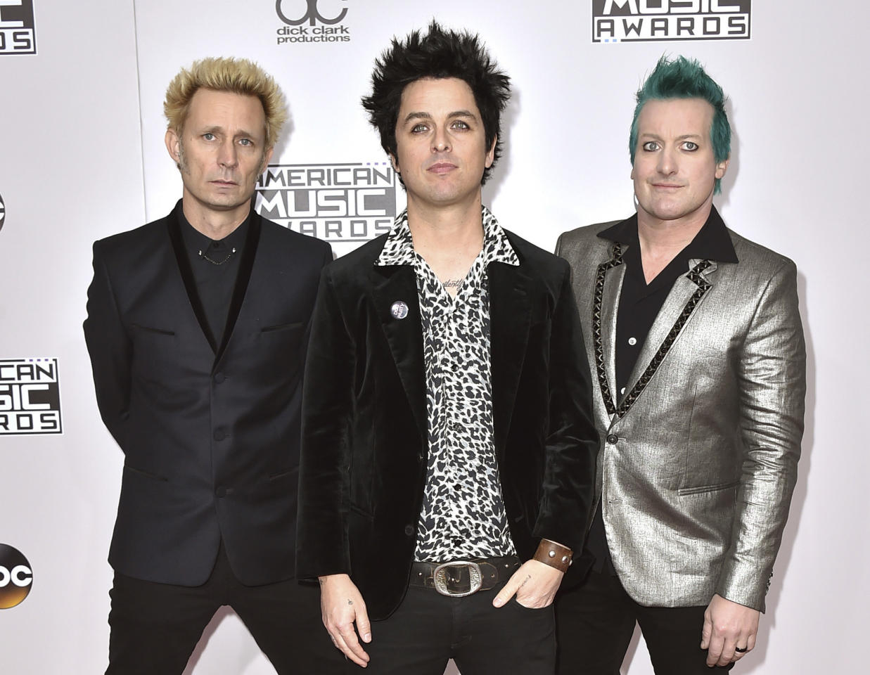 """FILE - In this Nov. 20, 2016 file photo, Mike Dirnt, from left, Billie Joe Armstrong, and Tre Cool, of Green Day, arrive at the American Music Awards in Los Angeles. The band will release their latest, """"Greatest Hits: God's Favorite Band,"""" on Friday. (Photo by Jordan Strauss/Invision/AP)"""