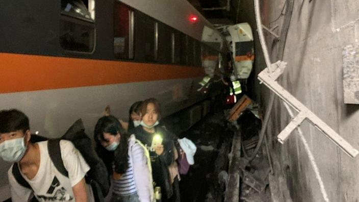 People walking next to a derailed train in the tunnel north of Hualien