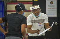 Election official Francis Vincent, right, gives instructions to a voter at Edmondson High School during the primary election in Baltimore, Tuesday, June 2, 2020. (Jerry Jackson/The Baltimore Sun via AP)