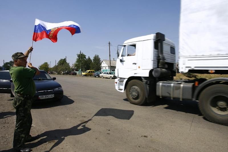 A local resident holds a Russian national flag as lorries, part of a Russian humanitarian convoy, cross the Ukrainian border at the Izvarino custom control checkpoint, on August 22, 2014
