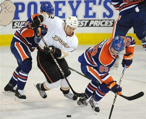 Edmonton Oilers' Corey Potter, left, and Sam Gagner, right, battle for the puck with Anaheim Ducks' Niklas Hagman during first period NHL hockey action in Edmonton, Alberta, on Friday, Jan. 13, 2012. (AP Photo/The Canadian Press, John Ulan)