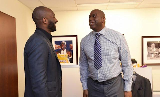 Kobe Bryant and Magic Johnson converse in Lakers offices. (Getty)
