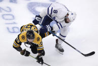 Boston Bruins left wing Brad Marchand (63) is knocked to the ice by Toronto Maple Leafs defenseman Jake Muzzin (8) during the first period of Game 7 of an NHL hockey first-round playoff series, Tuesday, April 23, 2019, in Boston. (AP Photo/Charles Krupa)