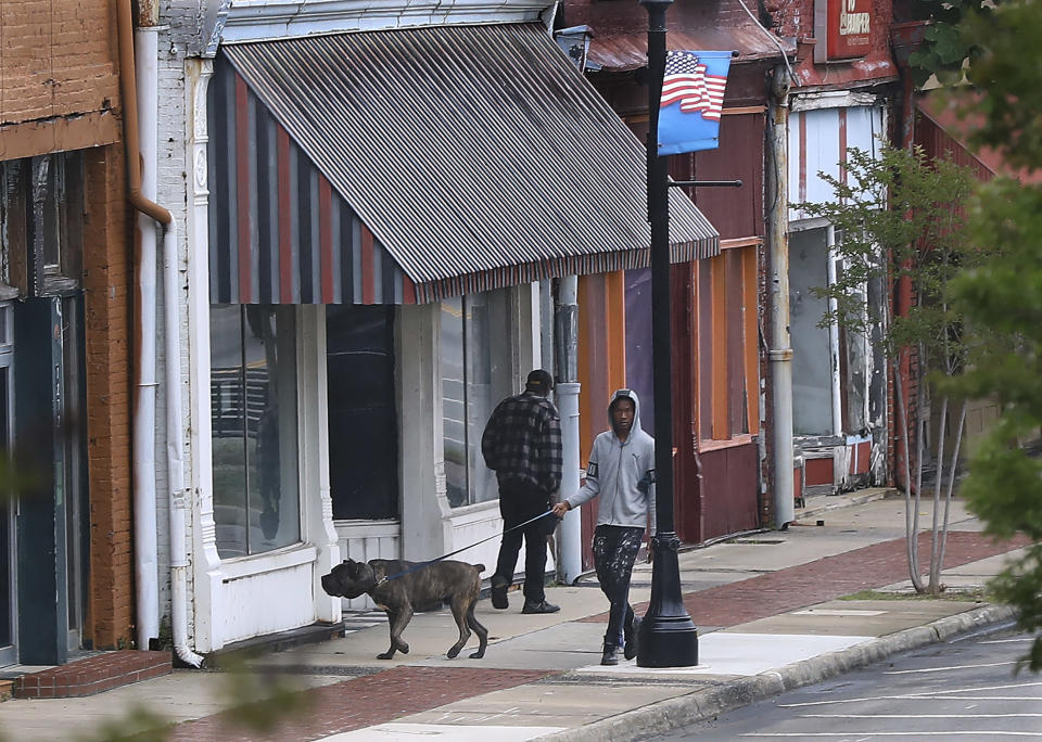 Local residents walk past businesses, many of which are empty, on W. Broad Street in downtown on Wednesday, May 20, 2020, in Sparta, Ga. Hancock County, halfway between Augusta and Macon has become a new coronavirus hotspot. (Curtis Compton/Atlanta Journal-Constitution via AP)