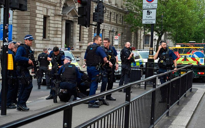 Firearms officiers from the British police detain a man on the ground on Whitehall near the Houses of Parliament - Credit: AFP