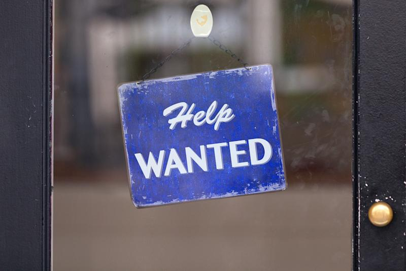 Close-up on a blue help wanted sign.