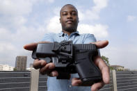"""Charles Blain, a new gun owner, poses with his holstered 9mm Glock 43 handgun, Monday, May 3, 2021, on the parking garage of his apartment complex in Houston. Blain also owns a shotgun and is currently completing his concealed carry license requirements to carry the handgun. Blain, who describes himself as a conservative, says """"pandemic-related unemployment crime"""" and repeated calls over the past year to release hundreds of jail inmates because of soaring COVID-19 infections pushed him to buy. (AP Photo/Michael Wyke)"""