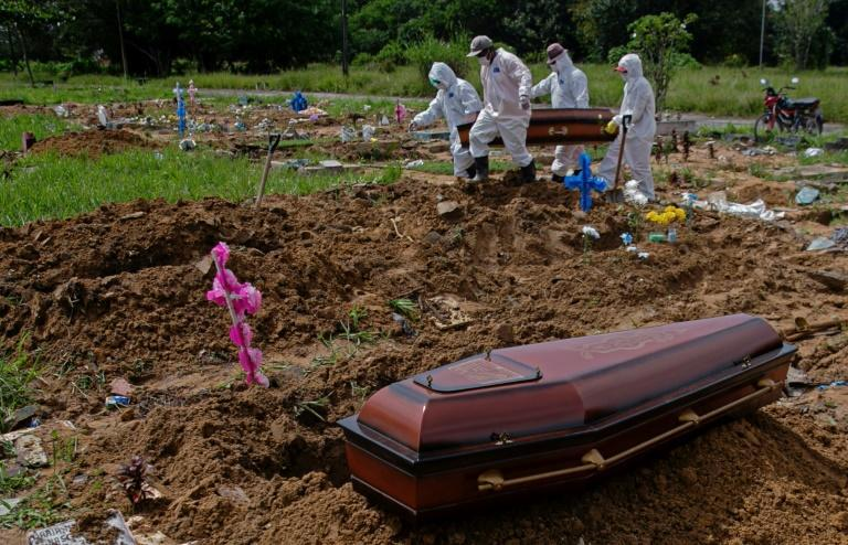 Workers in protective gear carry the coffin of a COVID-19 victim at the Parque Tapana public cemetery in Belem, Para state, in northeastern Brazil